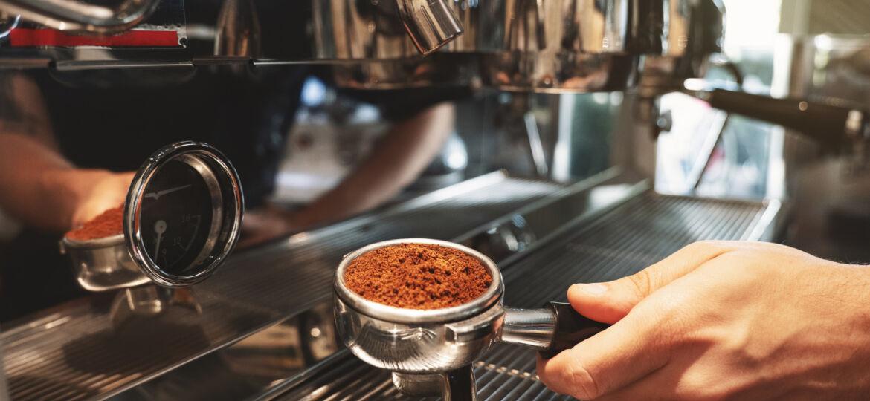 barista holding coffee holder with ground coffee near professional coffee machine close up